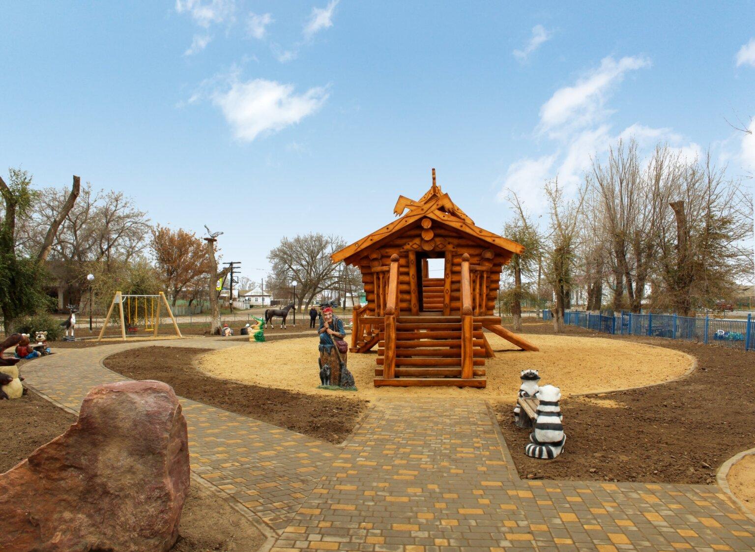 Детская площадка с резной скульптурой и избушкой на курьих ножках